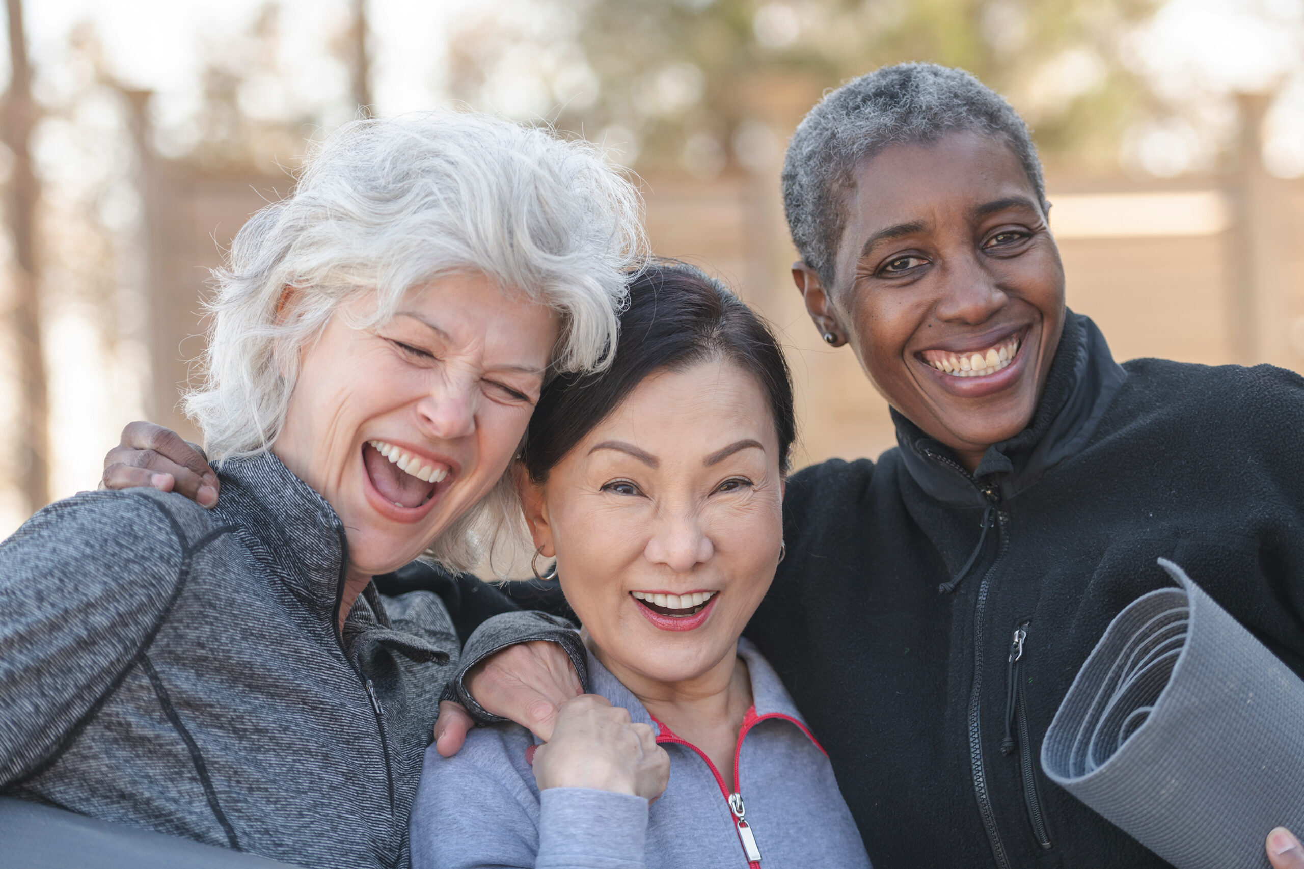 laughing older women with yoga mats