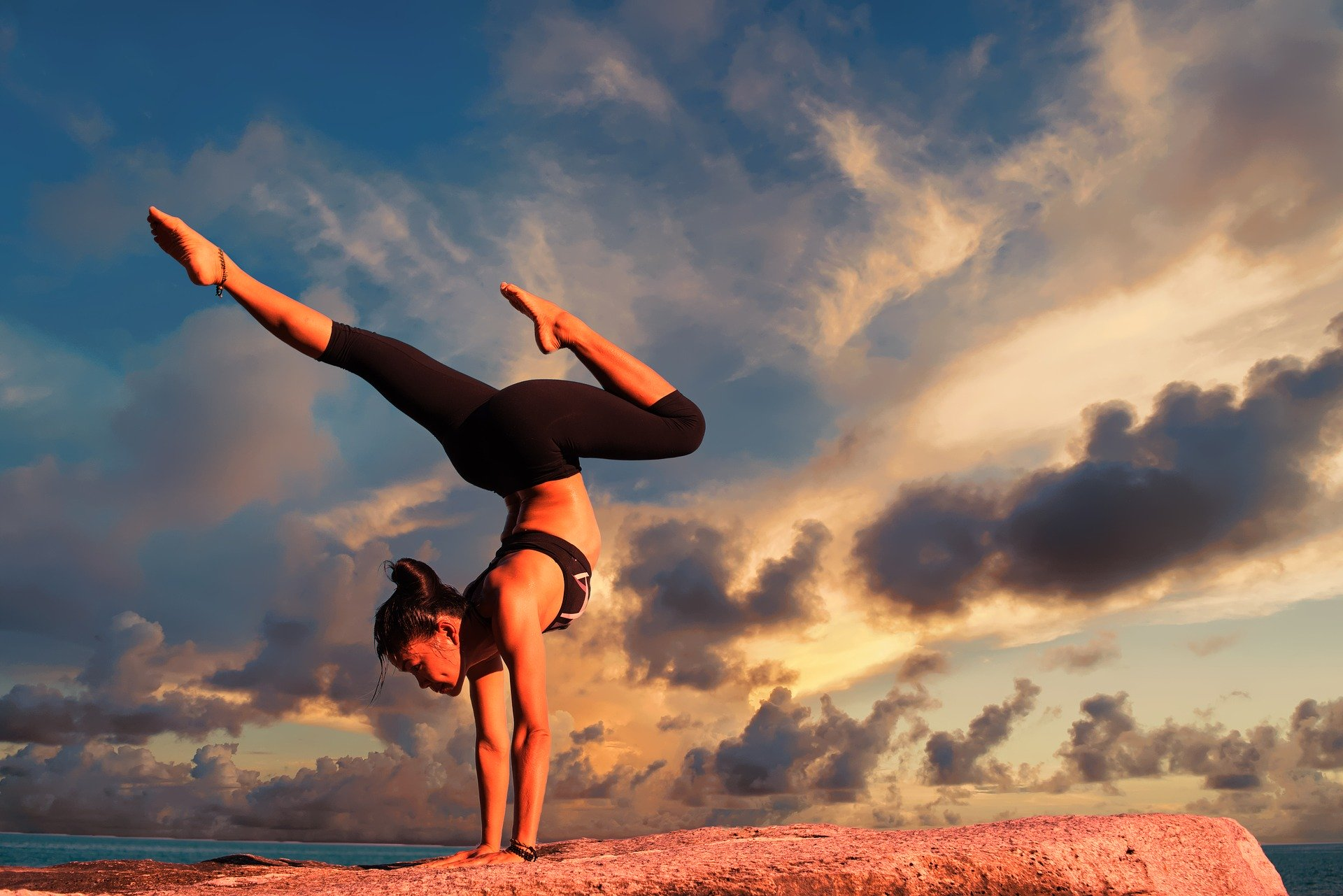young female doing yoga pose outside