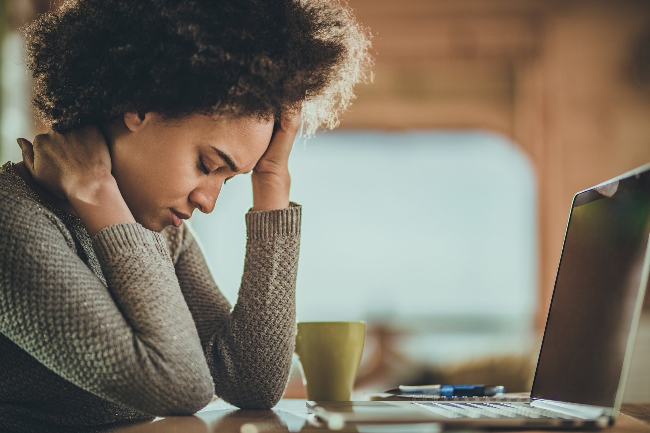 Young black woman experiencing a headache after working on laptop at home.