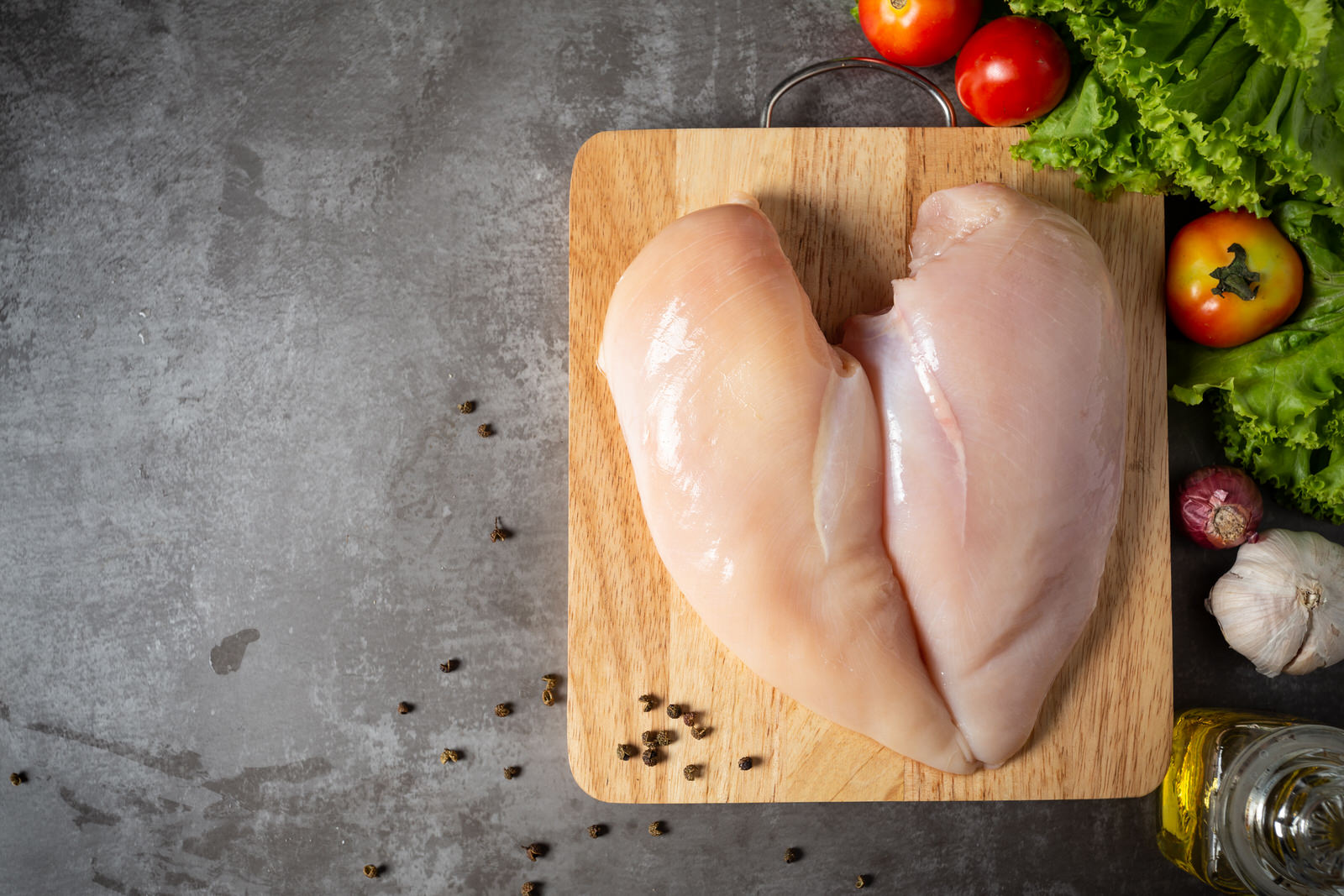 Raw chicken breasts on wooden cutting board.