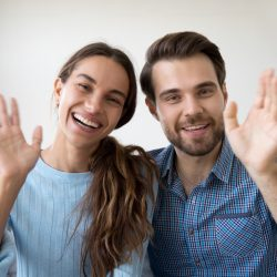 Man and woman smiling and waving