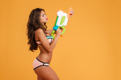 Portrait young girl in bikini holding water gun and posing