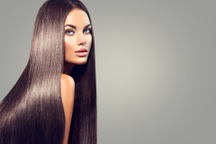 Beautiful long Hair. Beauty woman with luxurious straight black hair on dark background. Beautiful b
