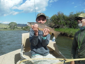 A young angler hoist's a fine Madison River brwon trout.