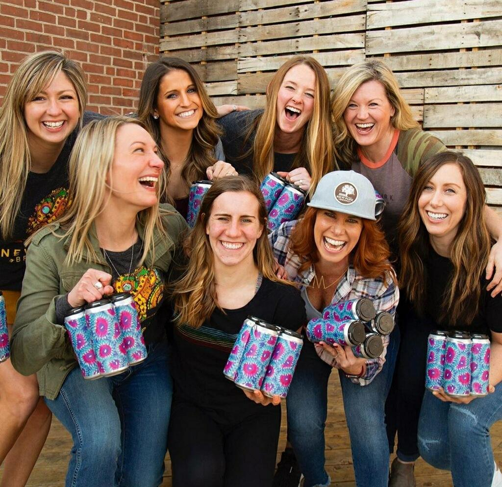 Group of women holding four packs of beer