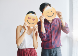Man and women holding emojis