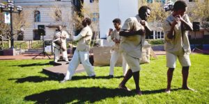 To the beat of Vernon Mobley's drum, the chorus (Chiedu Mbonu and Theophilus Timothy, representing American prisoners, background) and Robben Island inmates (Jamil Joseph and Ryan Fields, foreground) mime hard labor in The Island.