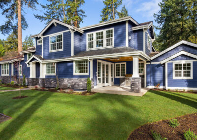 Beautiful luxury home exterior on sunny day with green grass, bl