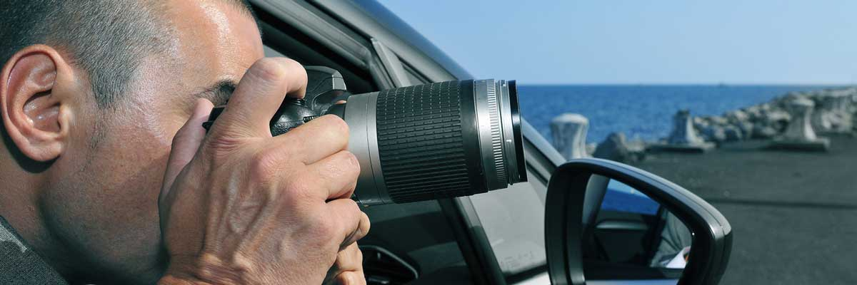 a detective conducting surveillance by taking photos from inside a car