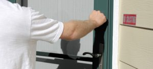 Man knocking on the front door of a home on a sunny day.