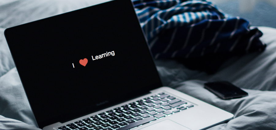 """Header graphic of a laptop on a bed with the words """"I heart (symbol) learning"""""""
