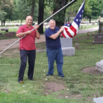 Br. Mo Krishna and W.B. Hal Cottrell putting up flags at Bellevue Cementary