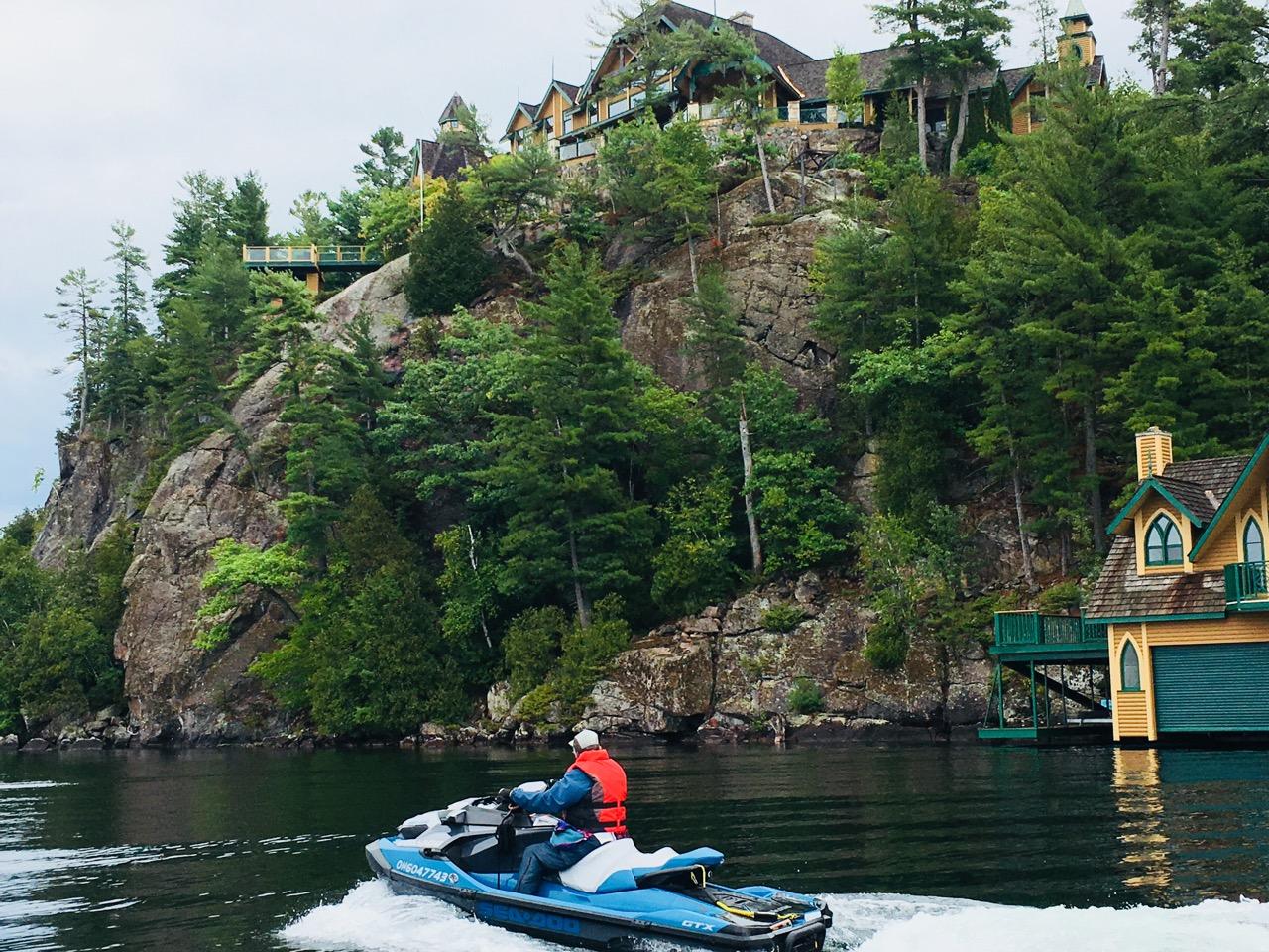 Cruising past cottage on a cliff on Muskoka fall Sea Doo tour