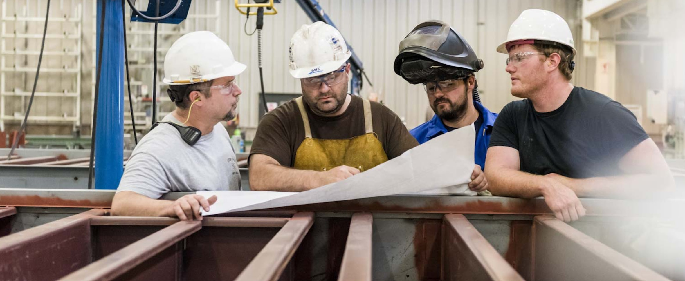 Collaboration - Four workers reviewing blueprints of a large enclosure they're building