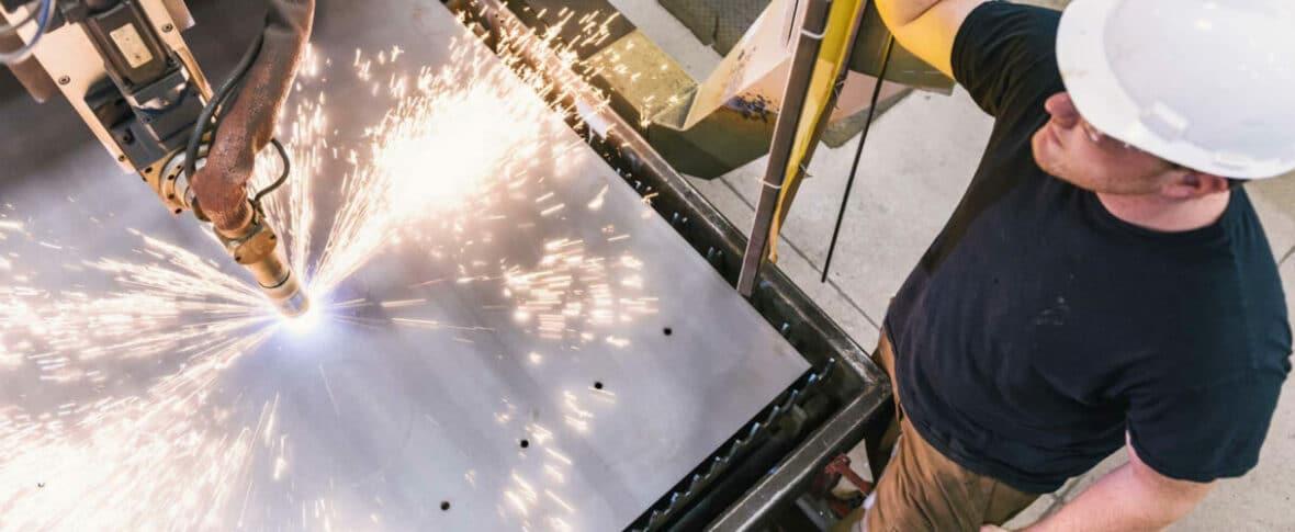 Man in hard hat watching welding machine