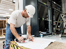 Man in hard hat reviewing blueprint