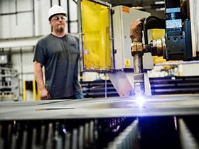 Man in hard hat observing welding machine