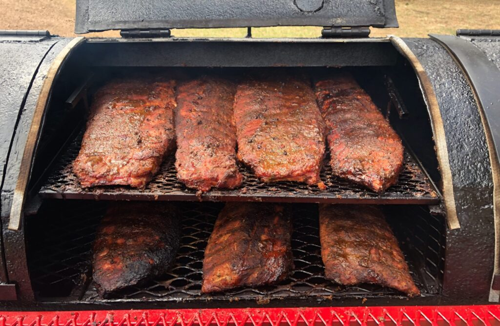 seven bbq ribs racks cooking in a smoker