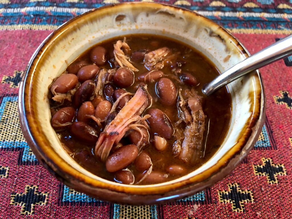 pinto beans with pulled pork in a bowl