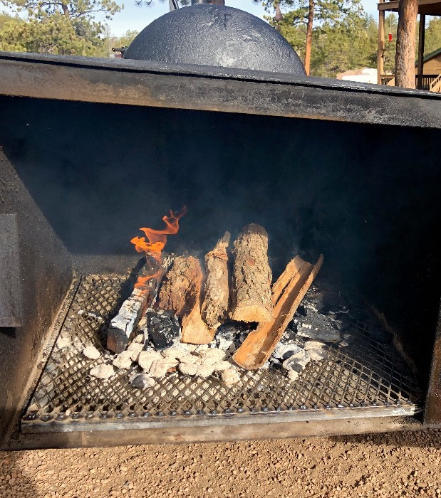 firewood burning in a BBQ smoker