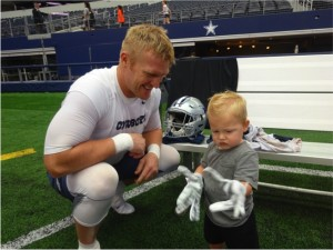 Dallas Cowboys Fullback Tyler Clutts puts his gloves on his son during Family Day at mandatory minicamp.  Mandatory Credit - Matt Thornton