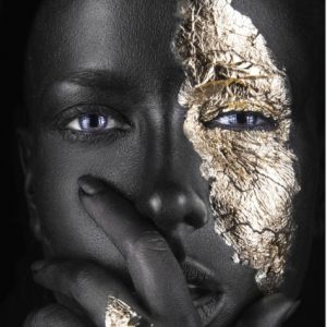 Beauty shot of a woman with fantasy half-face gold makeup.