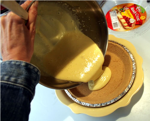 pouring key lime pie into shell