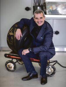 Bertrand Godin assis sur un petit chariot tenant un pneu de voiture de course autographié.