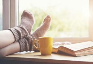Femme qui relaxe avec un café et un livre sur le bord de la fenêtre