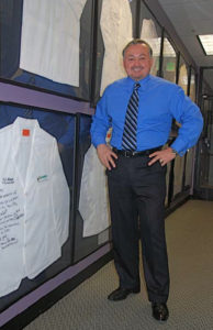 Brian with autographed smocks from some top doctor clients that he inspires and motivates