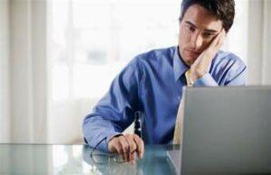 Dejected looking man looking at his computer screen