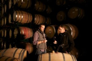 2 men standing in front of a wall of wine barrels