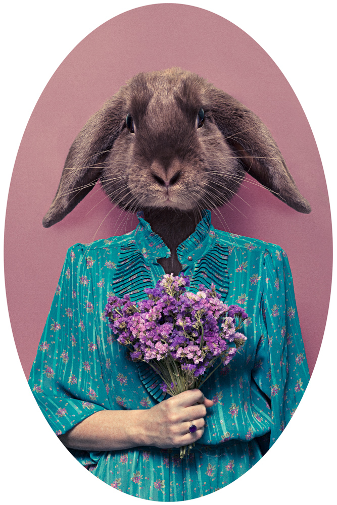 girl in flowerly blue dress with a rabbit head and holding flowers