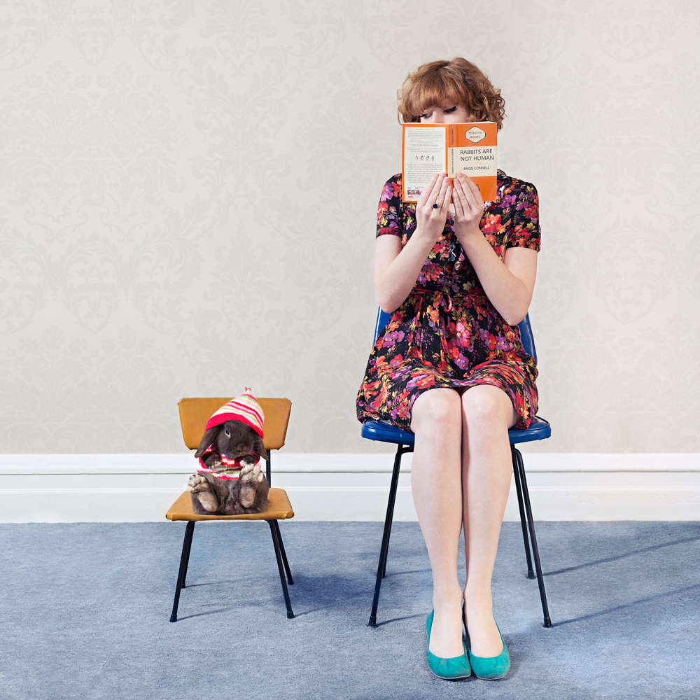 girl sitting on a chair reading a book with her rabbit sitting next to her on a chair