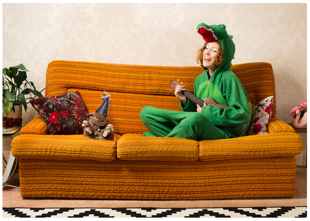 girl dressed in croc onesie playing a ukulele on the couch with her rabbit