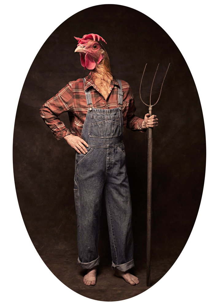 A farmer holding a pitching fork with a chicken head