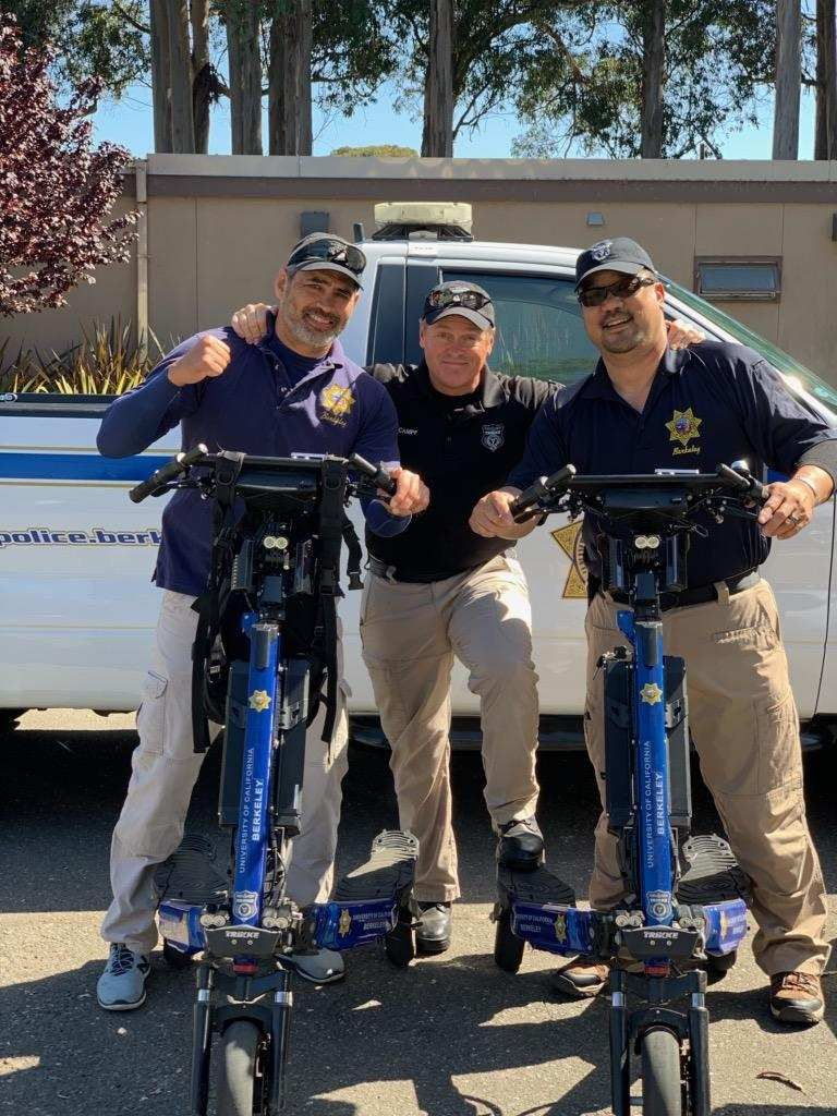 Three UCPD police officers stand with two Trikke Defenders.