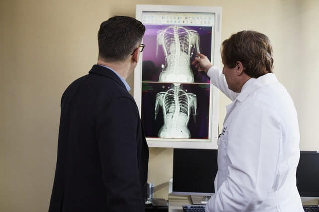 A doctor explains to a patient how the injury will affect his personal injury lawsuit.