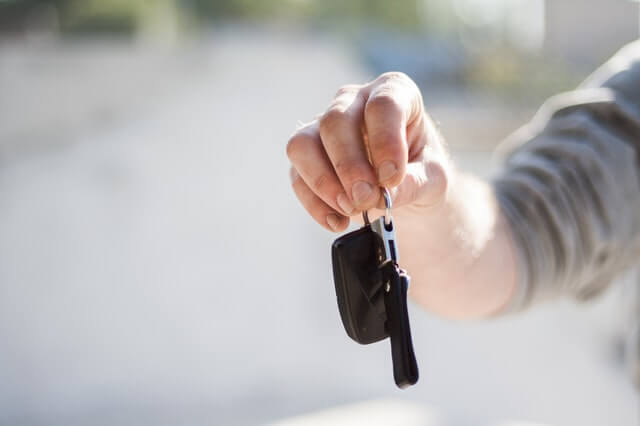 hand holding car key before rental car accident