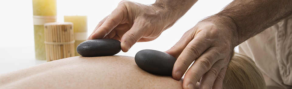 Caucasian middle-aged male massage therapist placing hot stones on back of Caucasian middle-aged woman lying on massage table.