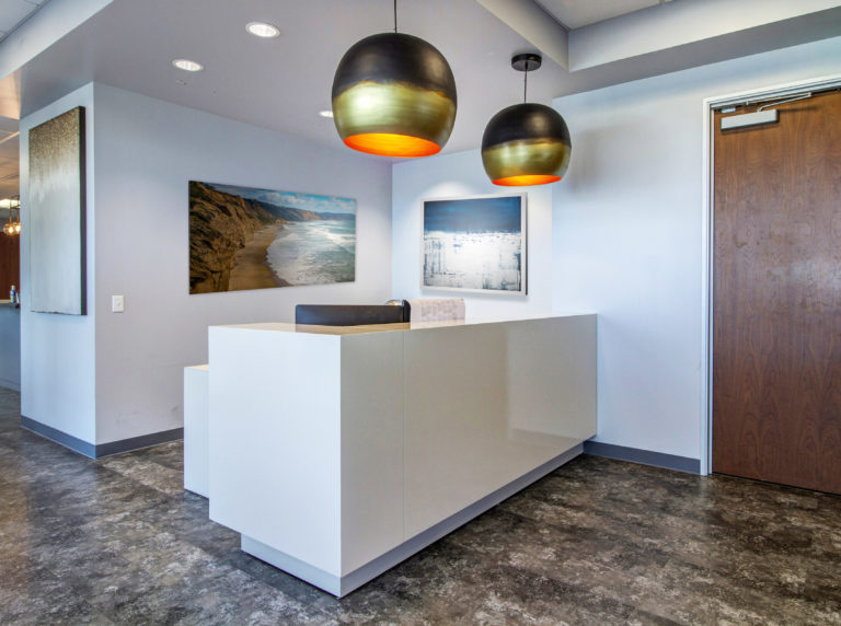 A white reception desk with two large orb lights above
