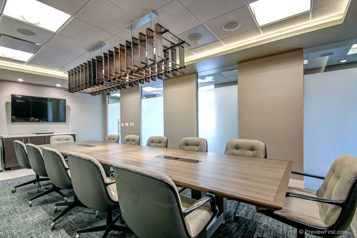A 12 seat conference table with a tv on the left end and an intricate wooden light fixture above
