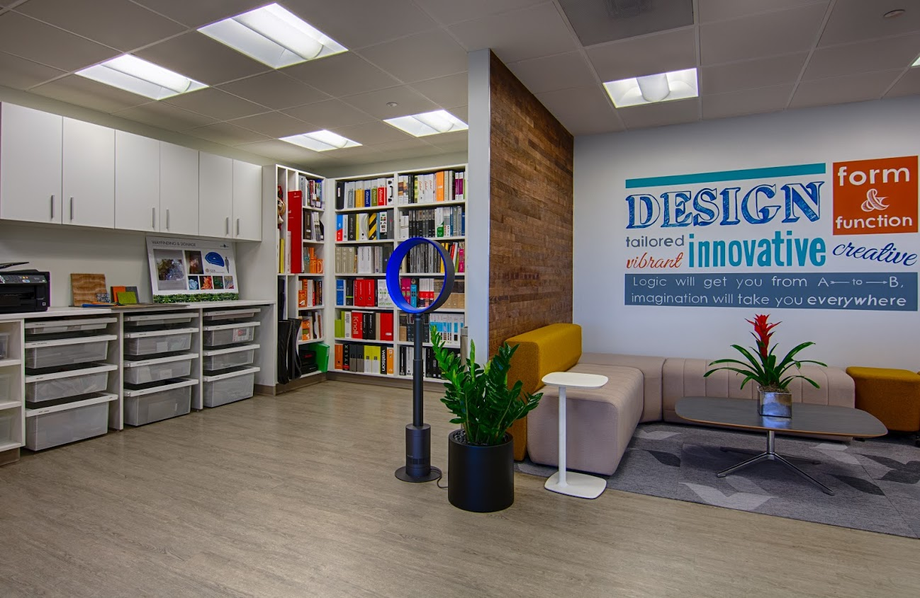 On the right, a sitting area with couches and a small wall. Behind the wall there is a library and storage area