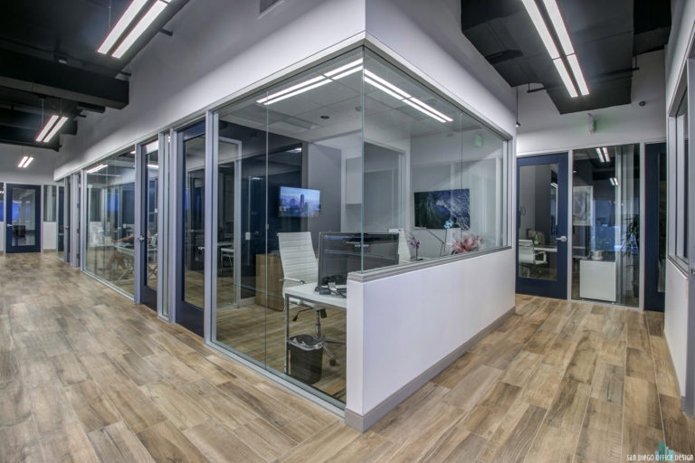 A row of offices with glass wall partitions, wood floors, and clean white walls between them