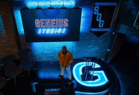 """Billy Gene standing on a black stage with a bright blue light up G on the stage, and a screen behind Billy that says """"Geneius Studios"""""""