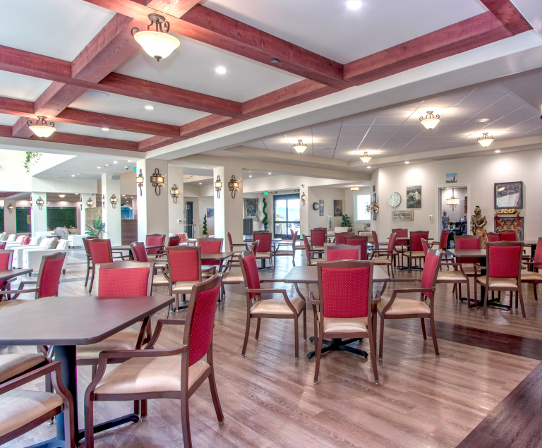 A large dining area with red backed seats and dark tables as far as the eye can see