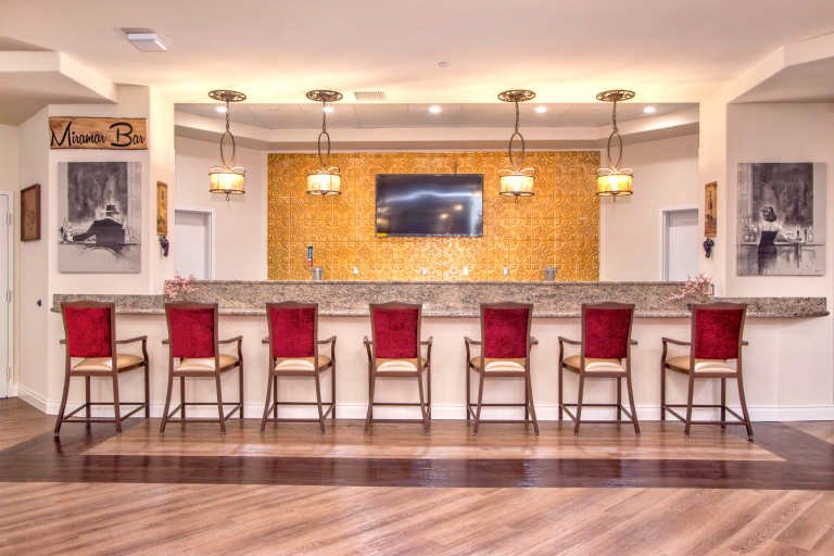 A luxury gold-backed bar with red-backed barstools
