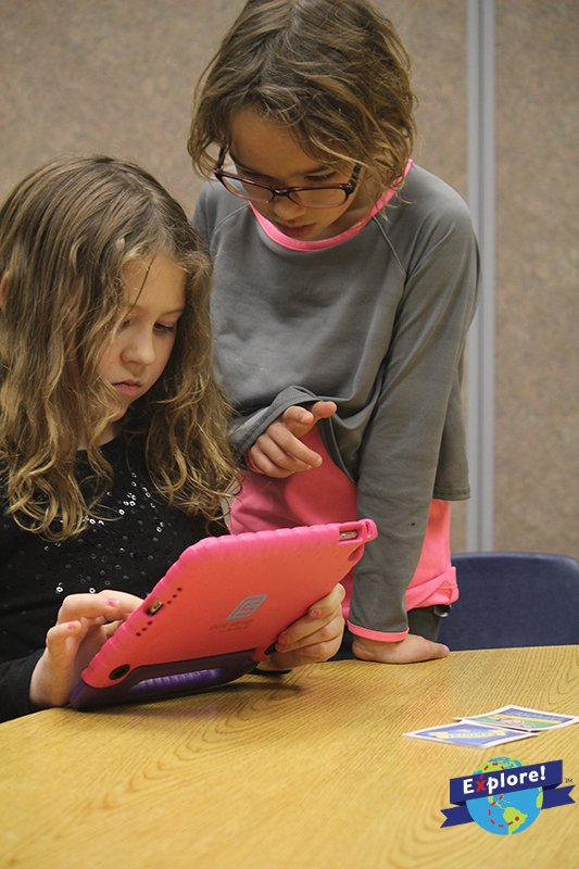 Two students play Explore Interactive's educational augmented reality mobile games.