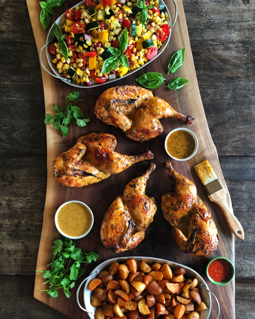 Two grilled piri-piri chickens cut in half and on a large wooden board. Served with roasted potatoes and a corn and tomato salad.