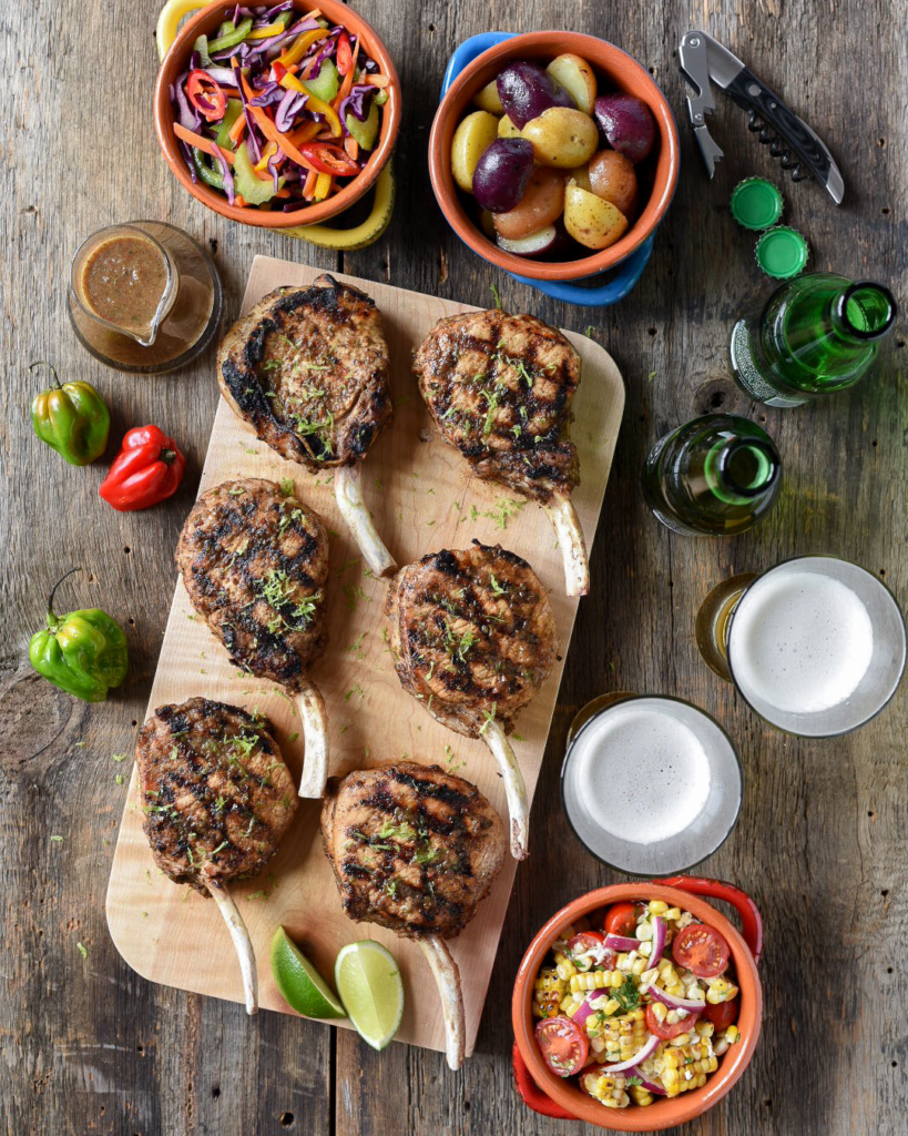 Six spicy jerk frenched pork chops shot top down on a wooden cutting board. Three colourful bowls are filled with different salads, beer bottles and glasse and hot pepers surround the board.